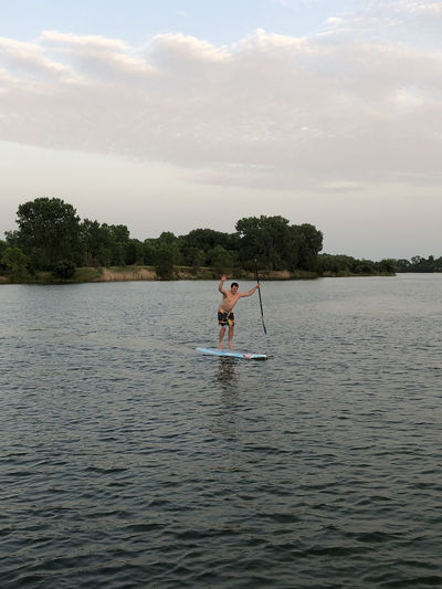 guy paddle boarding on lake Paddleboarding One Person Lake Water Waterfront Tree Real People Leisure Activity Plant Sky Lifestyles Beauty In Nature Nature Scenics - Nature Day Transportation Men Tranquility Oar Outdoors Having Fun Dusk Island Arms Raised Caucasian