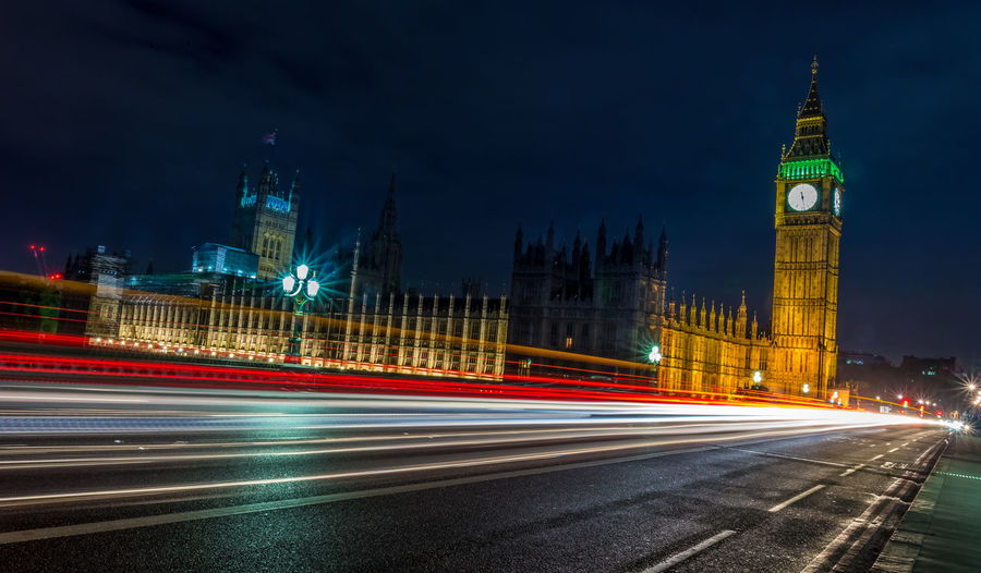 Light trails on street by big ben at night