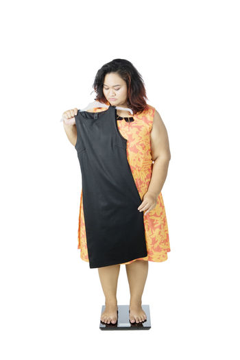 Full length of woman holding dress while standing on weight scale against white background