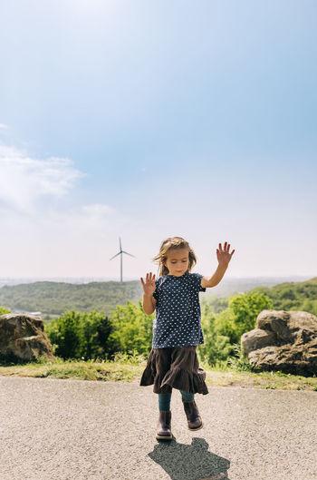 Full length of cute girl standing on land against sky