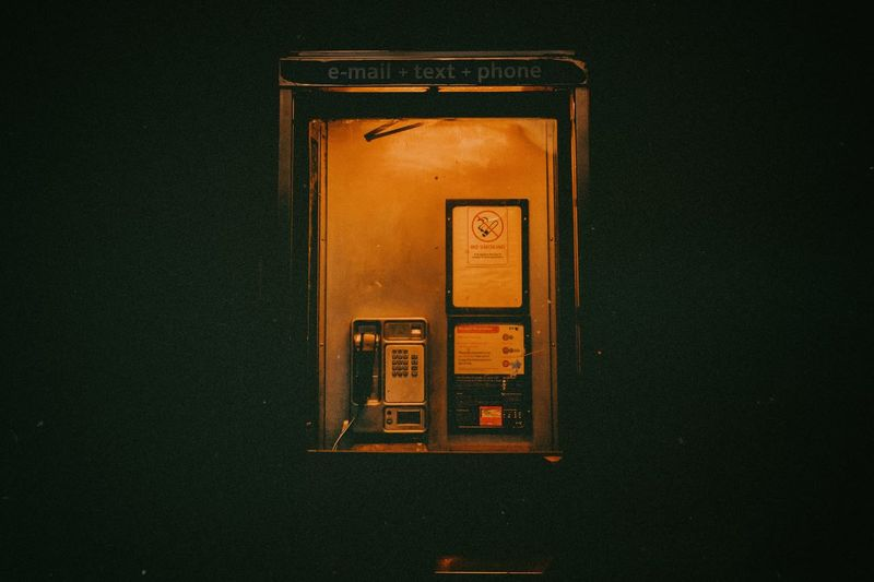 Illuminated telephone booth at night