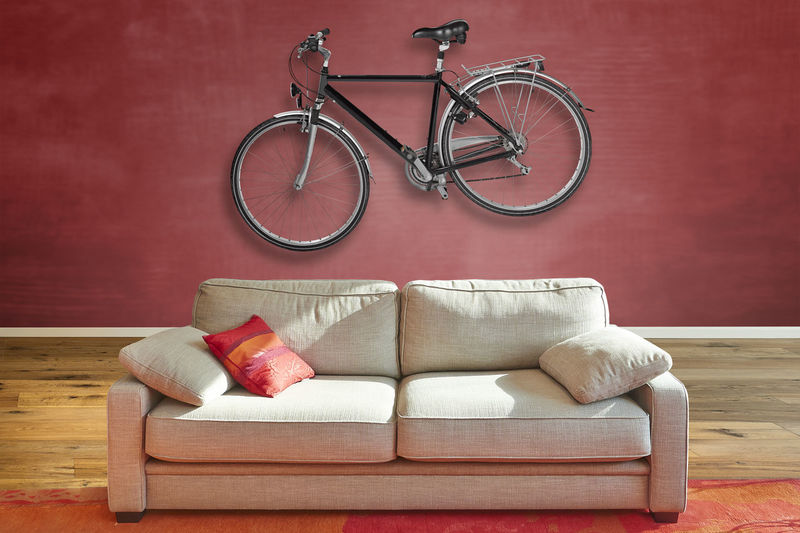 Elegant classical sofa from front in luxurious apartment with a hanging road bike on wall.