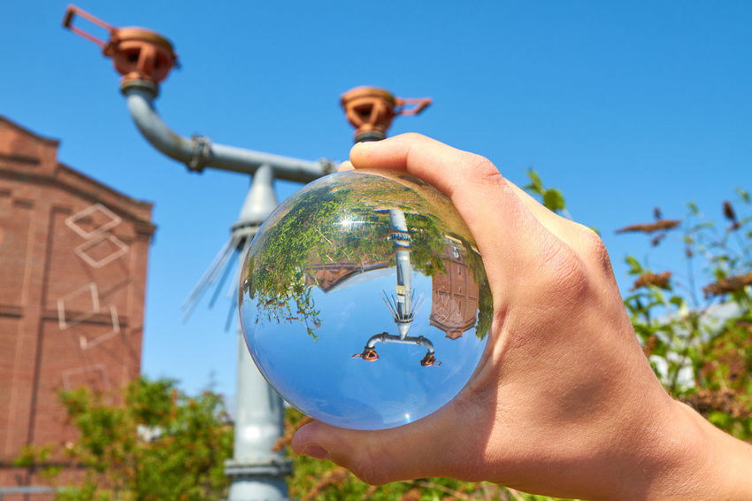 Protego cap Protego Protego Cap Sphere Architecture Blue Building Exterior Built Structure Clear Sky Day Finger Focus On Foreground Glass Glass Sphere Hand Holding Human Body Part Human Hand Nature One Person Outdoors Plant Real People Sky Sphere Sunlight