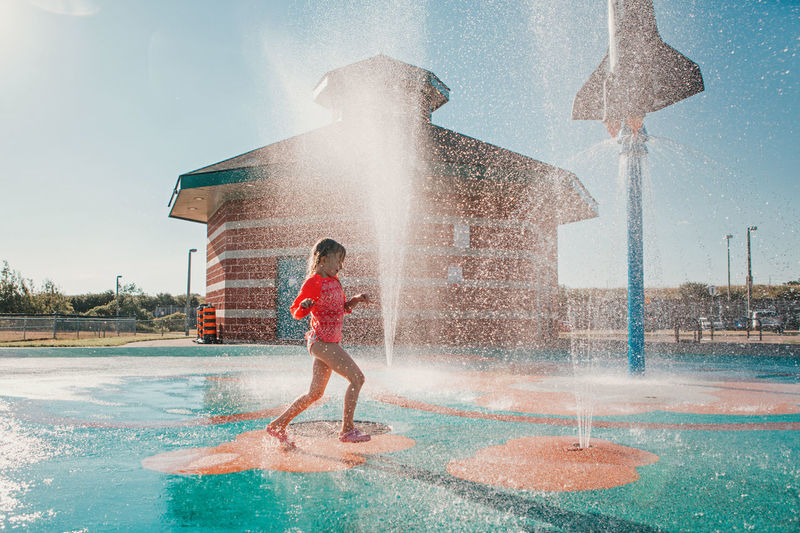 Cute adorable caucasian funny girl playing on splash pad playground on summer day. happy child