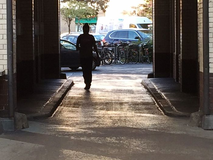 Rear view of man walking on sidewalk
