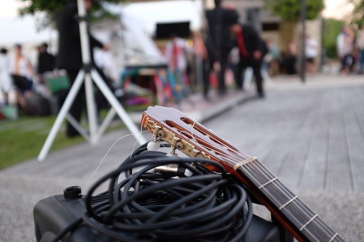 Close-up of electric guitar with cable on street