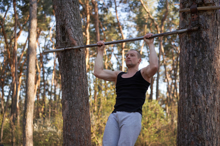 Young man exercising against trees in forest