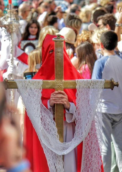 Penitente person holding cross in parade