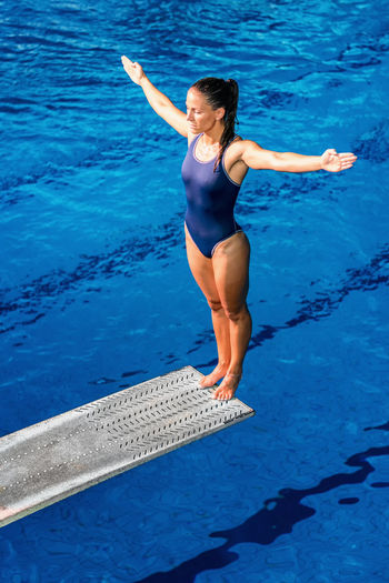Female Diver Standing On The Jumping Board Diving Diver Swimming Pool Woman Water Sport Training Competition Young Exercising Diving Board Board Above Action Swimwear Blue Activity Muscular Build Extreme Sports Caucasian Ethnicity Athlete Standing Concentration Pool Arms Outstretched