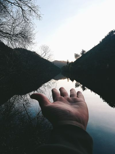 Cropped hand of person showing lake amidst trees against sky