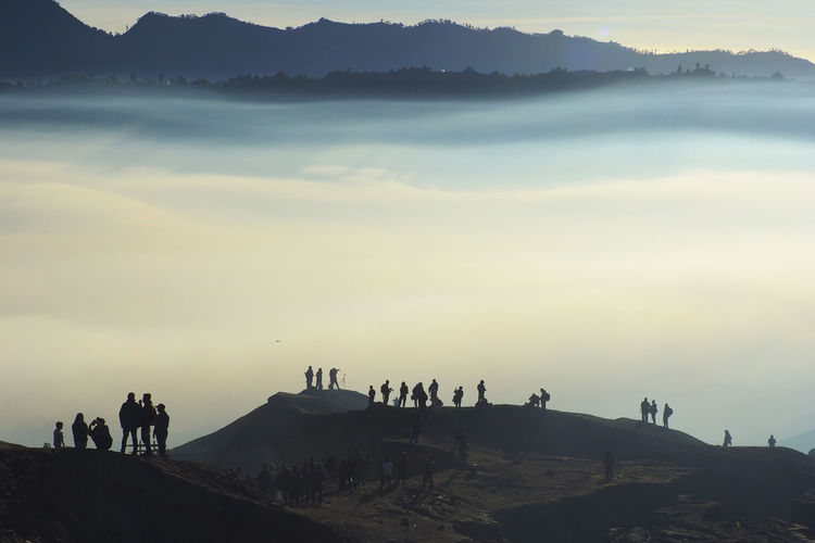 Silhouette People On Mountain Against Sky