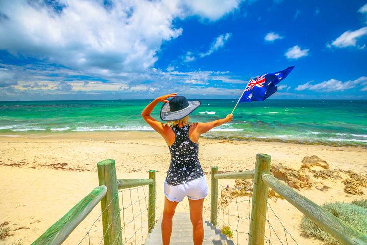Rear view of woman holding australian flag on steps at beach