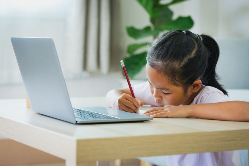 Rear view of girl using laptop on table