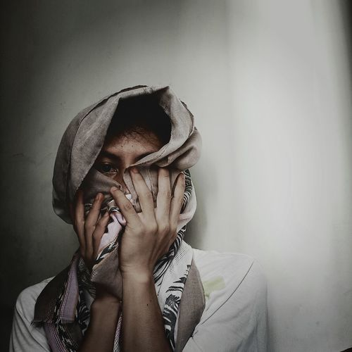 Portrait of man covering face with scarf against wall