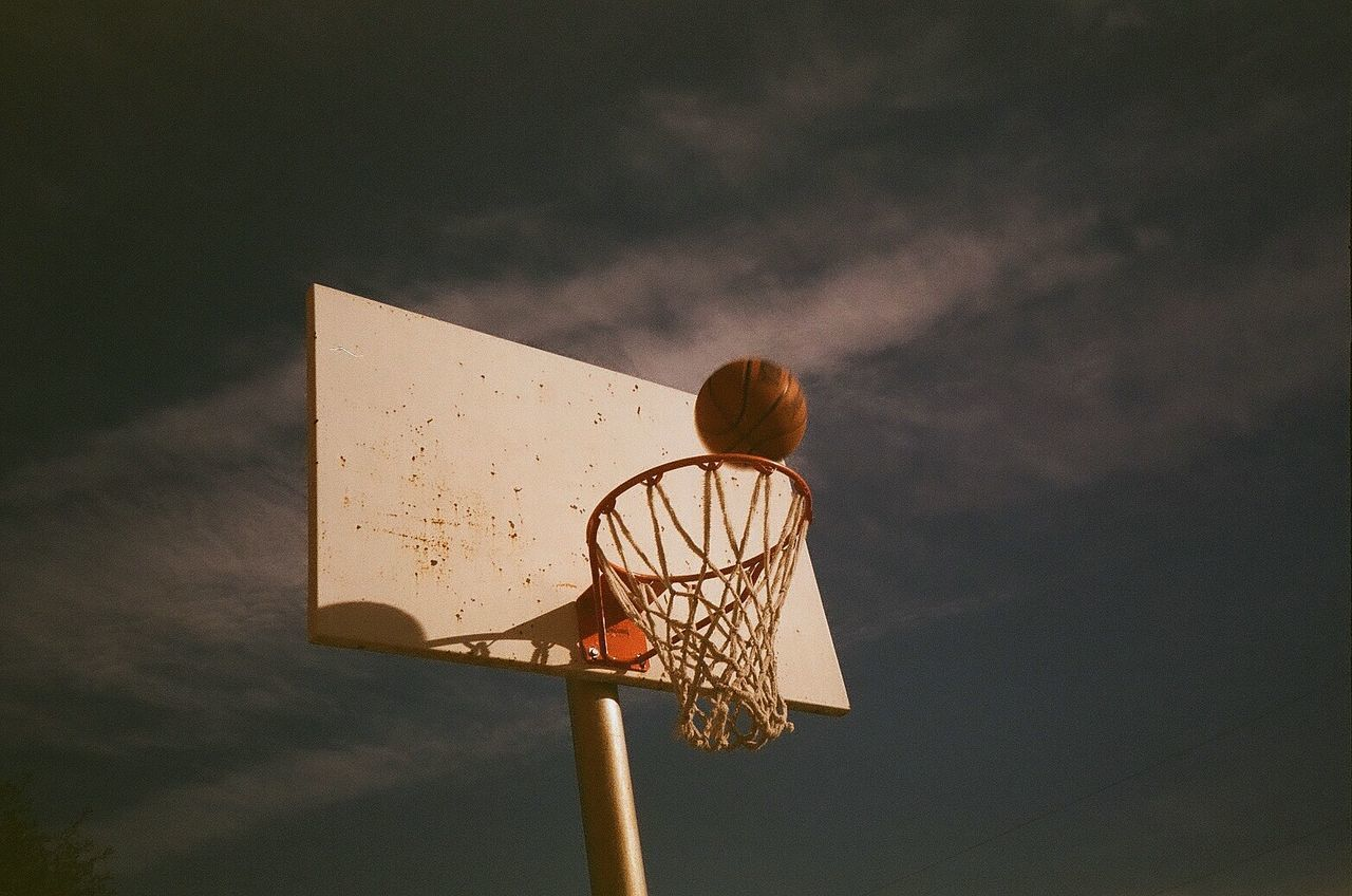 LOW ANGLE VIEW OF BASKETBALL HOOP AT SUNSET