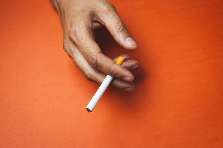 Close-up of cropped hand holding cigarette on orange background