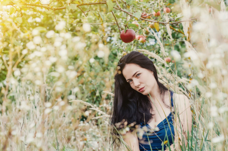 Portrait of beautiful young woman standing by fruit tree