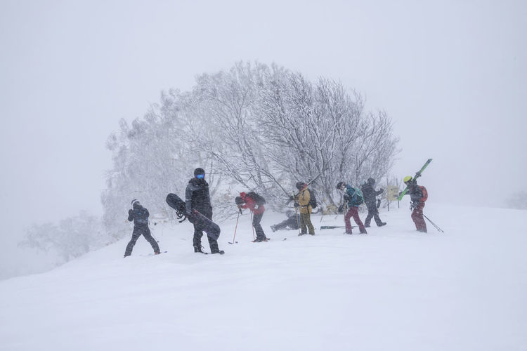 People walking on snow covered tree against sky