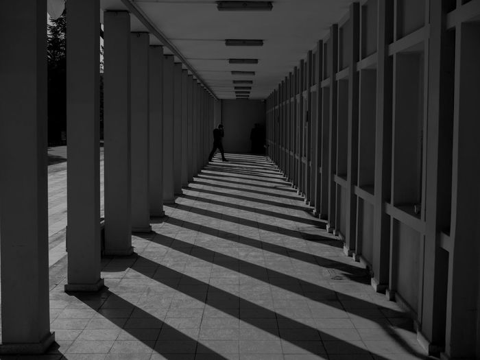 Architecture The Way Forward Direction Built Structure Arcade Corridor Building In A Row Architectural Column Indoors  Real People Staircase One Person Walking Diminishing Perspective Day Pattern Sunlight Railing Colonnade Tiled Floor