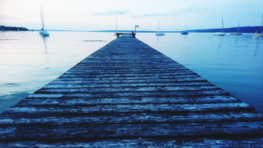 Surface level of pier over sea against sky
