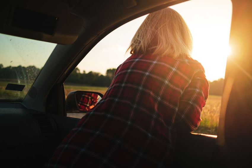 Adult Car Day Hairstyle Land Vehicle Leisure Activity Lens Flare Lifestyles Mode Of Transportation Motor Vehicle Nature One Person Outdoors Real People Rear View Sky Sun Sunbeam Sunlight Sunset Transportation Women