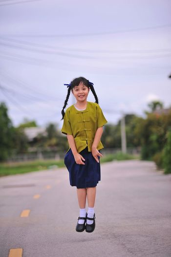 Portrait of girl jumping on road