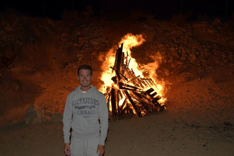 Portrait of young man standing by bonfire