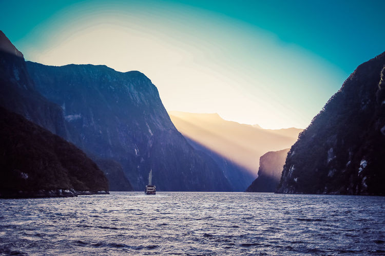 The sun setting over Milford Sound Water Mountain Waterfront Sky Beauty In Nature Scenics - Nature Sea Nature Tranquil Scene Tranquility Nautical Vessel Mountain Range Sunset Non-urban Scene Transportation Clear Sky Idyllic Incidental People Leisure Activity Outdoors