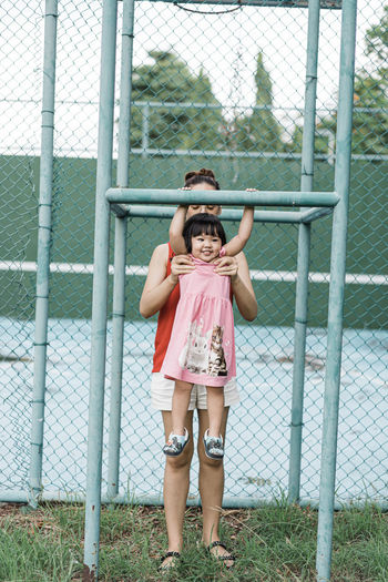 mon hold daughter on bar Child Full Length Childhood Fence Standing Front View Smiling Happiness Looking At Camera Females Boundary Barrier Day Portrait Girls Emotion People Casual Clothing Chainlink Fence Women Innocence Shorts Human Arm