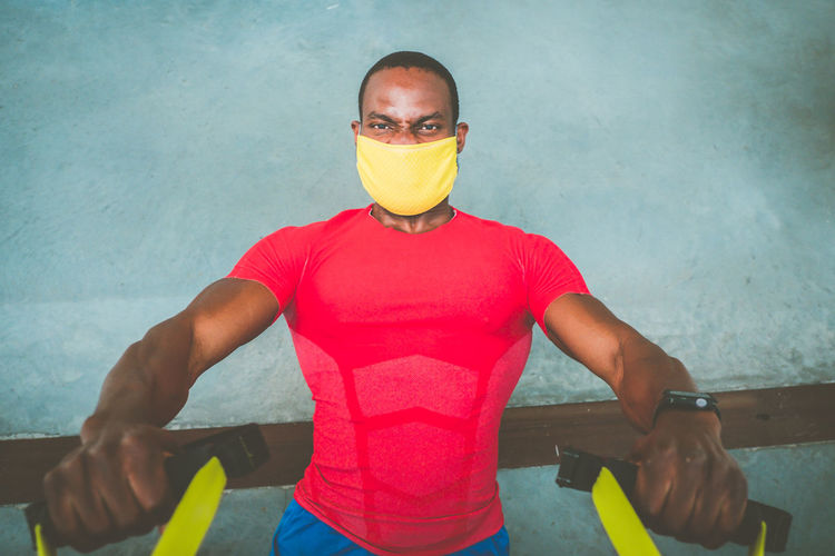 Portrait of man wearing mask exercising at home