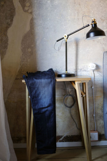 Electric lamp hanging on table against wall at home