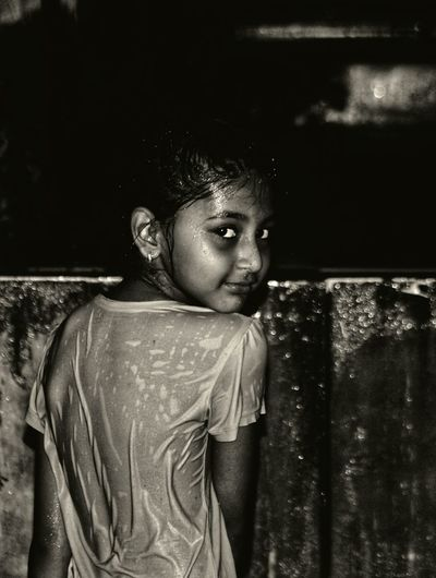 Portrait of wet girl standing outdoors at night