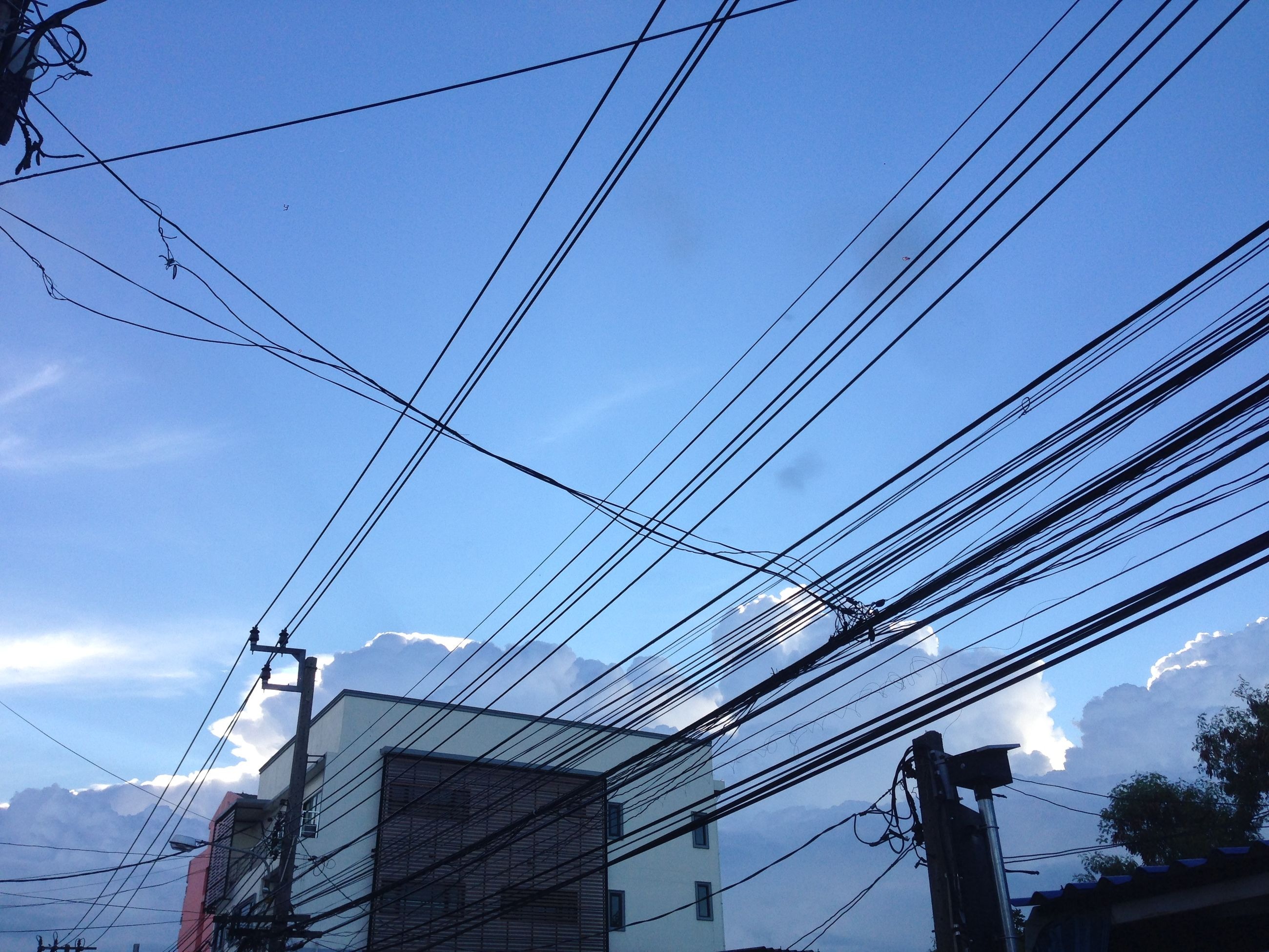 power line, electricity pylon, power supply, electricity, cable, low angle view, connection, power cable, fuel and power generation, built structure, technology, architecture, sky, building exterior, blue, wire, outdoors, no people, complexity, day