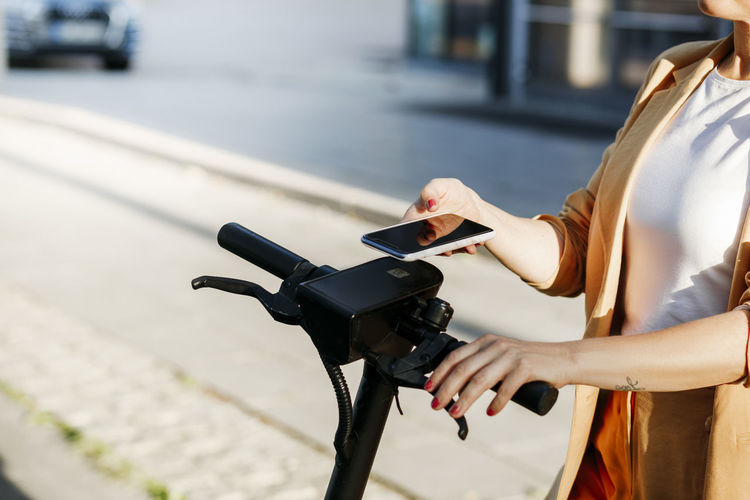 Midsection of woman with bicycle on street