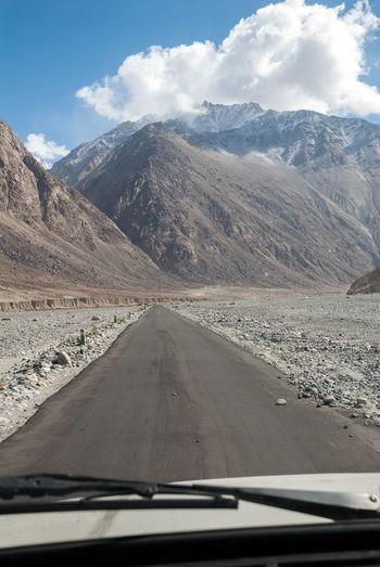 Road amidst mountains seen through car windshield