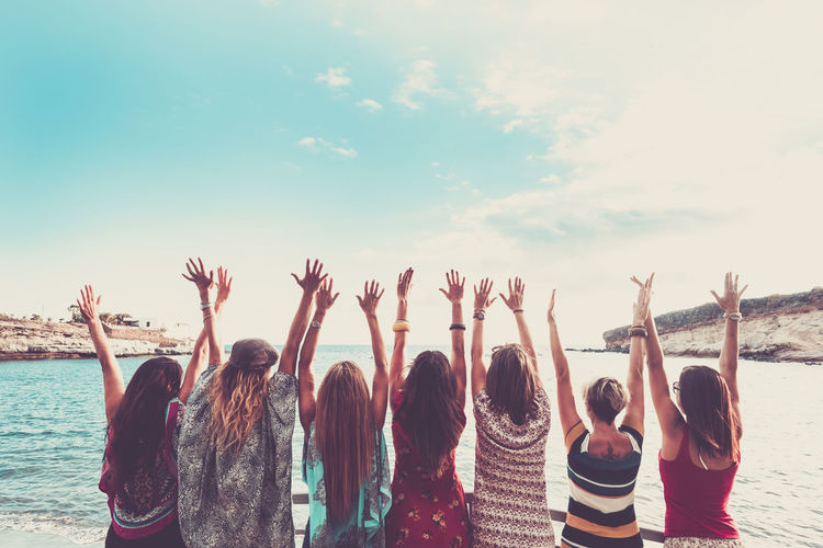 group of women enjoying and celebrate summer vacation all together saying hallo to the ocean and the nature Happiness Adult Arms Raised Beach Day Enjoyment Excitement Friendship Group Of People Human Arm Leisure Activity Lifestyles Nature Outdoors People Positive Emotion Real People Rear View Sea Seven People Side By Side Sky Togetherness Water Women
