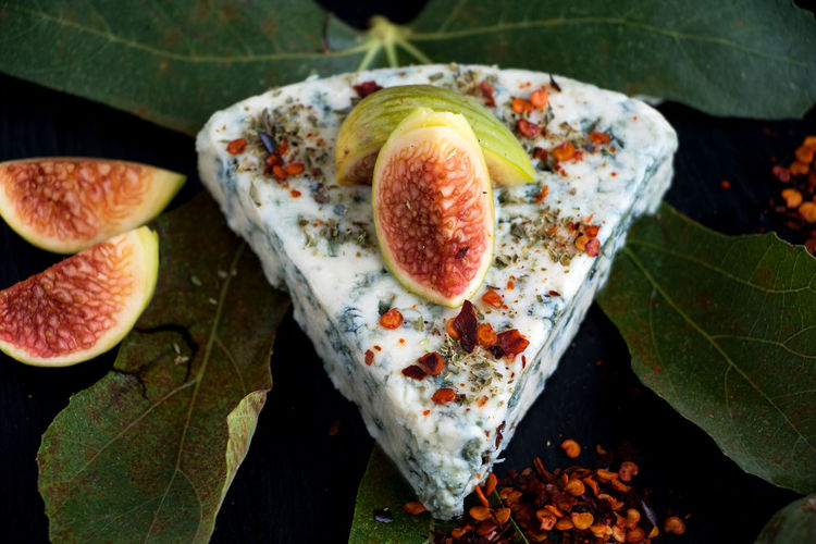 A piece of blue mold cheese with figs and paprika powder on a black slate board Danish Blue Cheese Aromatic Blue Mold Cheese Cheese Close-up Day Fig Food Freshness Fruit Gourmet Food Healthy Eating High Angle View Leaf Nature No People Outdoors Plant Part Ripe SLICE Still Life Table Traditionel Danish Triangle Wellbeing