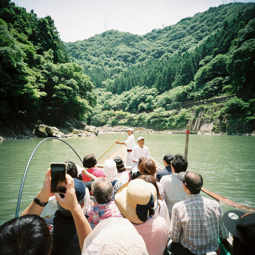 A group of tourists enjoy a traditional boat ride on a warm summer day outside the former Japanese capital of Kyōto. Arashiyama Fun Hozu River Hozugawa River Japan Sightseeing Tourists Travel Active Adult Bamboo Kyoto Mobile Phone Mountain Outdoors People Photographing Real People River Boat Sky Togetherness Water 京都 保津川 嵐山