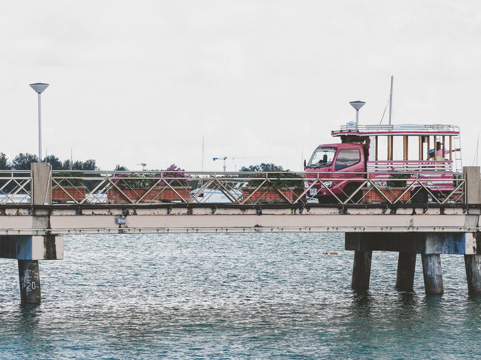 the local bus on bridge into the sea in harbor Building Travel Destinations City Travel Outdoors Bridge - Man Made Structure No People Day Connection Bridge Nature Transportation River Building Exterior Sky Waterfront Built Structure Architecture Water Local Bus