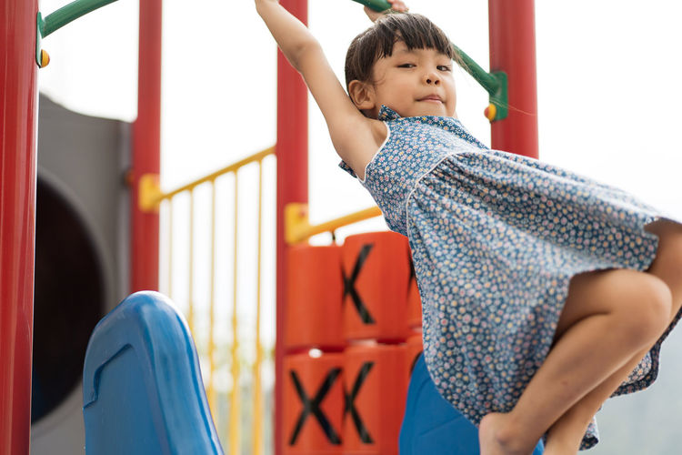 Asian girl playing at playground Boys Casual Clothing Child Childhood Day Emotion Focus On Foreground Happiness Innocence Leisure Activity Lifestyles Males  Men One Person Outdoor Play Equipment Real People Three Quarter Length