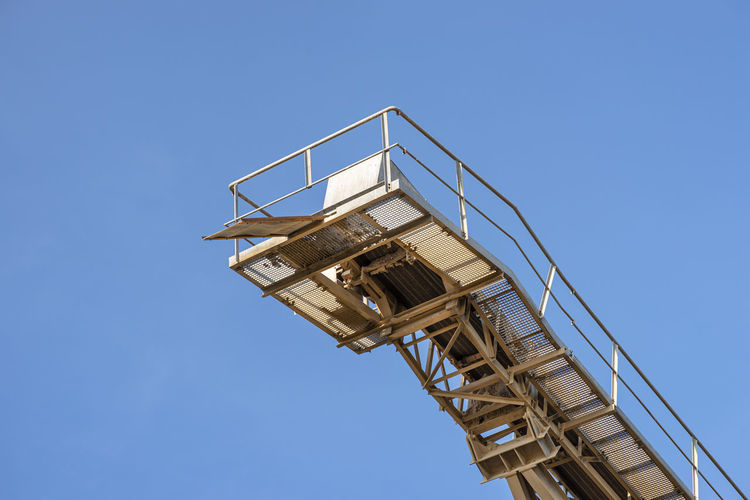 Conveyor belt for gravel against the blue sky at an industrial cement plant.