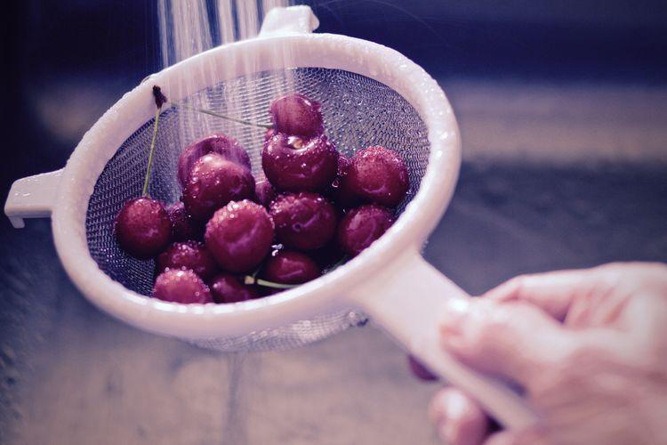 Close-up of hand washing cherries