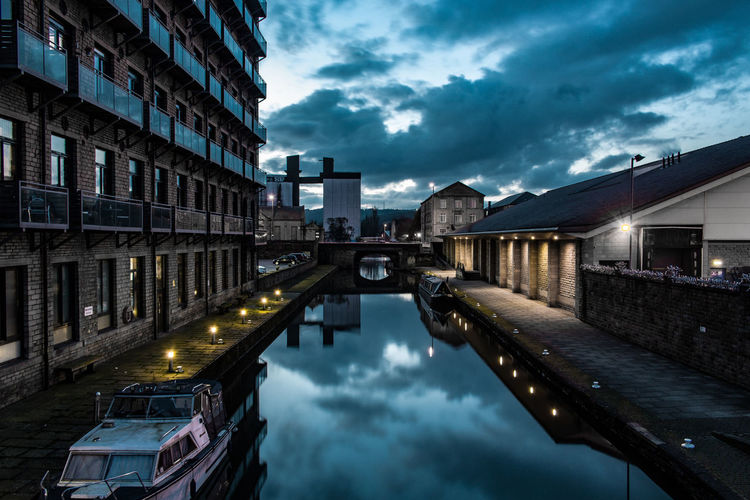 Reflection of illuminated buildings in canal at dusk