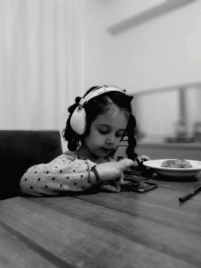 Cute girl listening music while having breakfast at home