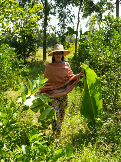 Woman standing by plants in basket against trees