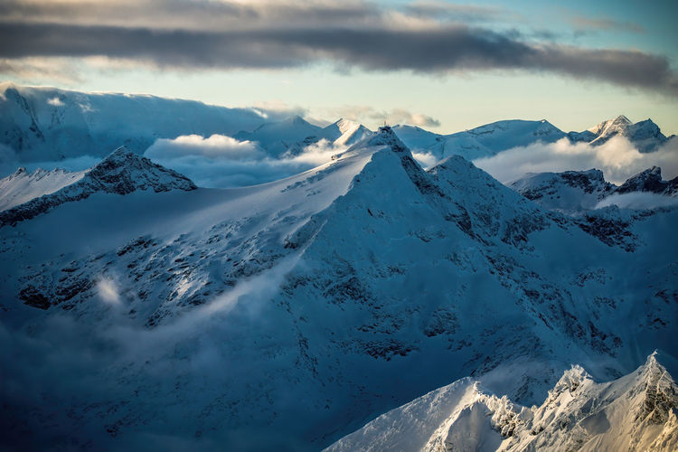 Dramatic sky above snow covered mountain peaks around mount sonnblick, austria.