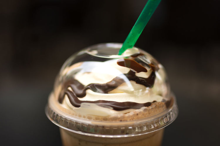 Close up of whipped cream and chocolate sauce on top of a Java Chip Frappe in a clear plastic cup and with a green straw. Caffine Chocolate Close-up Dessert Disposable Cup Drinking Straw Focus On Foreground Food Food And Drink Freshness Ice Cream Indulgence No People Plastic Cup Plastic Straws Ready-to-eat Sweet Food Temptation Unhealthy Eating