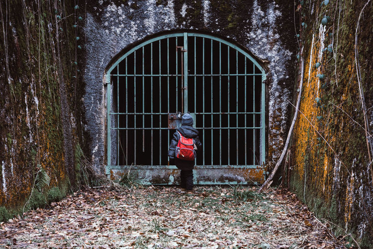 Gates to somewhere unknown Architecture Backpack Beauty In Nature Built Structure Child Creepy Darkness And Light Day Door Full Length Gate Headwear Horror Leisure Activity Lifestyles Mystery Nature Old One Person Outdoors People Real People Urban Young