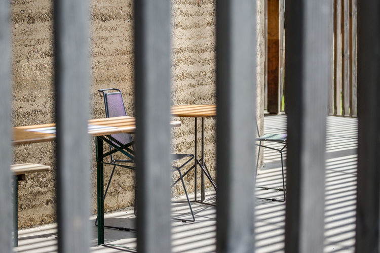 Empty Chairs With Table At Sidewalk Cafe Seen Through Fence