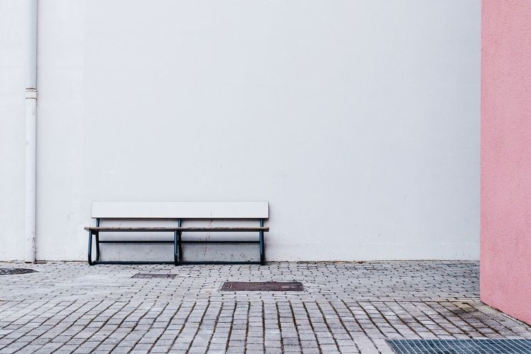 Empty bench on sidewalk against white wall